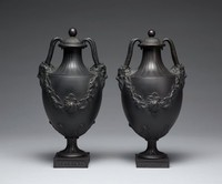 Pair of tall, footed covered vases in black basalt, urn shaped and resting on small square plinths decorated with a repeating geometric pattern on each side, the foot and stems as well as the body above the shoulder and neck are engine turned, the lower body with acanthus leaves that extend upward and the main body with swags of leafy grape vines and bunches of grapes, each has two handles comprised of satyr masks, whose long horns curve up and around and attach to the lip of the vase, with fluted covers with ball finials (not identical).