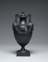Small black basalt footed vase resting on a small square plinth decorated on each side with a molded pattern of ovals, the foot and stem engine turned and with a band of overlapping leaves at the edge, the lower body of the vase with graceful acanthus leaves extending upward and on each side a garland of leafy grape vines and bunches of grapes, the two handles are formed of satyr masks, whose conjoined horns curve up and attach to the lip of the vase, above the shoulder and on the neck the decoration is likewise engine turned, the conforming cover is also engine turned and has a ball finial (possibly not original).
