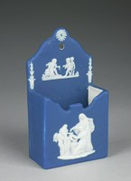 Small match box of white jasper with dark blue dip and white relief decoration, the box square with open top and with an extended back panel with central hole used to hang the box on the wall, the box with central white jasper bas relief of Cupid as Oracle – the God of Love depicted as Oracle divining the future for a young maiden – and the back panel with white jasper bas relief of cupids and on either side a leafy stalk and above the hole a daisy.