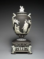 """Large vase of black and white jasper resting on a tall, heavily ornamented pedestal base, the urn-shaped body with round foot decorated with applied white anthemion motifs, the two handles in the form of serpents holding an egg above a small relief of Medusa, the main body with the relief """"Apotheosis of Virgil"""" after John Flaxman featuring winged figures holding wreaths, a seating figure with a lyre and another with a long horn, in the center the figure of Virgil, classically draped and holding a scroll, the cover is surmounted with the figure of Pegasus, the pedestal base is square with truncated corners, at each is a griffin and on the sides are two small reliefs with classical scenes and two small reliefs with fruit and garlands, the border below the upper edge of the pedestal includes scrolling foliage and anthemion motifs."""
