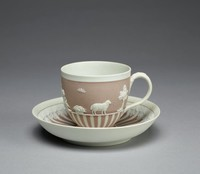"""Cup and matching saucer of buff-colored lilac jasper dip, the cup footed and the lower part of the body engine-turned to reveal a lilac and white striped pattern, the upper body with white relief on the lilac ground, the figures drawn from the """"Domestic Employment"""" series and Cupids after designs by Lady Elizabeth Templetown, with a reeded loop handle, the interior of the cup polished; the conforming saucer with similar engine-turned decoration in a lilac and white striped pattern, the edge with a border of applied white acanthus and stiff leaf ornament."""