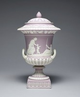 Covered urn of lilac jasper dip with white jasper relief decoration, on square plinth decorated with anthemion motifs, the round foot with egg and dart motifs, the lower body with modified egg and dart and the main body with relief scenes from the life of Achilles, on one side the birth of Achilles and on the other the dipping of Achilles in the River Styx, below the lip a band of grapevines, egg and dart on the lip and a band of stylized leafy motifs around the shoulder, the conforming cover with stiff leaf motifs and pinecone finial.