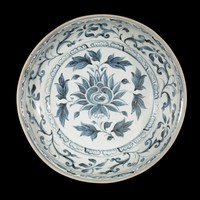Dish with lotus spray in center surrounded by band of scalloped lotus petals, floral meanders and scrolling on rim, lappets on exterior, all painted in underglaze cobalt blue oxide