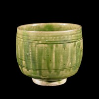 Glazed stoneware beaker with glaze streaks representing lotus-petals on exterior.