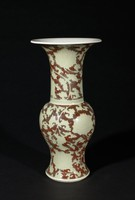 Baluster vase with copper and celadon glaze. Vase is incised in shallow relief with large peony scrolls, against a background painted in copper red. The floral designs are covered with a very pale blue celadon glaze.