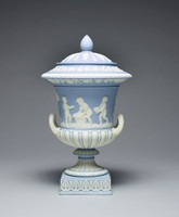Covered urn of solid light blue jasper with white jasper relief, resting on a square plinth decorated with anthemion motifs, the foot with acanthus leaves, the lower body with modified egg and dart decoration and the main body with the relief scene of six Bacchanalian boys in a landscape, on one side they are gathering grapes in baskets, on the other they are drinking wine, with a band of grapevines and leaves below the edge and egg and dart motifs on the edge with a band of laurel leaves and berries just below the lip, the conforming cover with stiff leaf motifs and a pinecone finial.