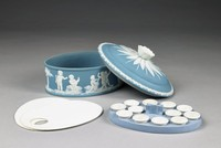 """Ladies' covered paint box of light blue and white jasperware, oval in shape, the main body with stippled ground and decorated in relief with scenes from """"Setting Out on the Hunt,"""" """"Bringing Home the Game,"""" and """"The Arts,"""" with groups of putti with dogs and hunting accoutrements, carrying game, and playing instruments, the slightly domed cover with acanthus border and sunflower finial with applied leaves against stippled ground; the interior outfitted with two white paint palettes (not original) and a blue holder with twelve small white paint cups (also not original)."""