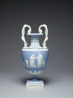 """Vase of solid light blue jasper with white jasper relief decoration resting on a square white molded jasper plinth, the foot round and with applied acanthus relief decoration, with beading at the joint, the lower body with a band of stiff leaf motifs (one of which has sprung from the body during firing), the main body with figures from the """"Domestic Employment"""" series designed by Lady Elizabeth Templetown, with a thick band of overlapping laurel leaves on the shoulder and acanthus leaves on the neck, with a large band of beading at the lip (the cover missing, originally had two handles)."""