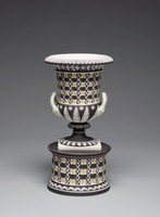 """Small urn-shaped, two-handled vase mounted on a round drum-shaped pedestal, the pedestal of black jasper dip, engine-turned in Wedgwood's """"diced ware"""" checkerboard pattern of black and white with yellow relief decoration in the form of quatrefoils and white relief decoration in the form of scrolling leaves and leafy elements, the vase rests on a plain white square plinth and has a round foot enhanced with a leafy border and overlapping acanthus leaves on the vase's stem, both likewise in white relief, the lower body of the vase with an acanthus leaf and star pattern, the upper body decorated in the same """"diced"""" pattern as the pedestal with a band of leafy vines directly below the lip in white relief, the lip with a border of white stylized floral motifs, the two white jasper handles terminate in rams' heads."""