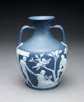 Copy of the Roman glass Portland Vase (now in the British Museum) in slate blue-gray jasper with white jasper relief decoration, the two-handled vase in the shape of an amphora, one side shows on the left the image of a nude male emerging from an architectural structure and grasping the arm of a recumbent, draped female figure holding a sea serpent, above her is a flying Cupid holding his bow and arrows, to the right is a tree and a nude male figure resting his right leg on the stump, his chin in his right hand, which is resting on his knee; on the other side left is a draped male figure seated on a rocky structure next to a column, he looks over his shoulder to his left at a central figure, a draped, recumbent female, lying on the rocky base, looking slightly left and with her right arm reaching over her head, behind her and to the right is the figure of a draped seated male looking over his right shoulder at the central figure; underneath each handle is a bearded mask; the base with the image of a cloaked figure, head lowered, wearing a wrapped headdress, with right arm raised to face, in the background foliage. The white jasper used for the relief decoration has been given a blue tint prior to being pressed into the molds.
