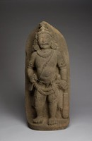 Well-carved guardian figure three quarters in the round with deep recessed undercuts; naturally worn