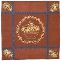 "Large ""Gunboat Quilt"" of brown silk taffeta, at its center an embroidered basket overflowing with appliqued flowers and two tiny strawberries and a small butterfly, surrounded by an embroidered wreath of similar flowers, like flowers adorn each of the four corners, the quilt front is divided by a geometric pattern of two vertical and two horizontal bands of small dark-blue taffeta squares, the back a medium brown polished cotton, the edges bound with blue taffeta."