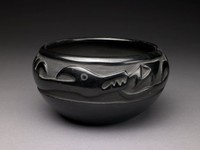 Glossy blackware bowl with Avanyu (water serpent) in raised relief within deeply carved recessed band around bowl; tongue of water serpent in shape of zig-zag terminating in arrow. Areas of the recessed band around Avanyu in matte black.