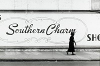"""This black and white photograph shows a black woman walking on a sidewalk in front of a large-scale sign reading """"Southern Charm."""" The sign is painted in a dark color on the white wall of a brick building, and in the foreground a small amount of street is visible."""