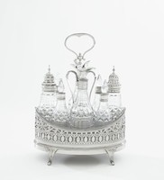 Delicate nine-piece cruet set comprised of a silver frame with wooden floor, the frame canoe-shaped with four fluted, slightly scrolled feet and pierced sides in a pattern of scrolls, ovals, and bands of leafy elements with pierced floral motifs at each end, with lightly engraved bands of squiggles and dots and on one side an empty oval reserve, in the middle a two-notched, long-stemmed handle with a pierced, eight-sided piece that holds the glass cruets in place, with urn-shaped finial and extended, heart-shaped handle, the frame holds eight cut-glass cruets, or glass bottles, of varying sizes, four with silver collars and glass stoppers, two with domed silver covers pierced in a dotted or dash pattern, and two with engraved, hinged, silver lids with duck-billed spouts and long, curved fluted handles, the cruets fit snuggly into the frame.
