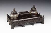 Heavy rectangular inkwell of cast iron resting on a total of ten block feet, the base in the form of a Gothic architectural structure comprised on each long side of a colonnade of three ogee arches and on each short side of two ogee arches with blind Gothic trefoils, crockets, and leafy finials with small battlements in between, each corner a kind of shield with leafy motifs, the inkwell proper with two openings for sand and ink (the glass inserts now missing) with covers decorated with organic motifs and stylized leaf finials, in the middle a central well with tapered and fluted body and leafy lip and foot (the cover is missing).
