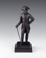 Cast-iron statuette of King Friedrich II of Prussia (1712-86), standing with his right leg casually bent, his left hand on his hip and his right hand holding a walking cane, wearing civilian dress with the Order of the Black Eagle on his left breast, the statuette on a small square, stepped pedestal.