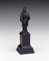 Statuette on tall base.