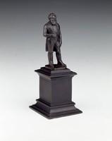 Statuette on tall plinth.