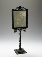 """Delicate porcelain lithophane in cast-iron holder, the lithophane depicts the scene """"Brautwerbung"""" (Courting the Bride), model number 229 in the Plaue Porcelain Manufactory's Preis-Courant, and shows on the left a young woman seated under a tree chatting with a young man in knickers, who casually leans on a barrel with his legs crossed at the ankles; the lithophane holder with a square base decorated with scrolling foliage and with a smaller square pedestal upon which rests the foot of the lithophane comprised of leafy foliage, the stem of the lithophane in the form of a column that is enveloped by stylized acanthus fronds, the frame above, which can be removed from the stem, is rectangular and rests on two scrolling, leafy vines which emanate from the stem, with pierced leafy motifs on either side and the top with pierced, scrolling decoration and a shell-like finial."""