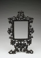 Ornate lithophane holder of rectangular shape the frame highly decorated with intertwining, scrolling grape vines with leaves and bunches of grapes, at the bottom two vines scroll down and around to form legs upon which rests the holder, with a third leg in the back for support.