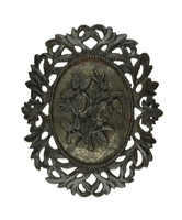 Oval brooch with pierced frame of scrolling foliage, the central medallion with applied rose branches on a polished steel plate.