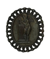 Small oval cast-iron jewelry fragment with a pierced and beaded frame, the central medallion with the figure of a winged cherub standing at an altar.