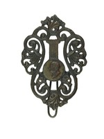 Cast-iron key hook in the form of pierced lyre-shaped S-scrolls and stylized palmettes, in the center a small medallion with the portrait head of a man in profile left.