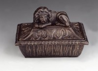 In the shape of a tub, the cover with relief decoration and a recumbent lion as knob.