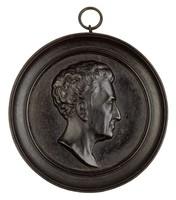 Head in profile right, in cast-iron frame.