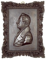 Bust in profile left in civilian dress with medal, in decorative, cast-iron frame.
