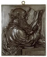Half figure of a bearded man reading a folio.