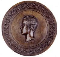 Head in profile left in decorative cast-iron frame.