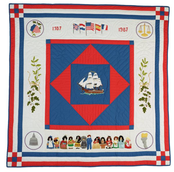 Large, mostly red, white and blue cotton embroidered and appliqued quilt designed to commemorate the bicentennial of the signing of the US constitution in 1787, in the center a blue square edged in red and with a smaller red square at an angle inside it, within this a blue square with the image of a full-rigged ship on its way to the New World, at each corner a roundel that includes representations of the three branches of the US government as well as liberty illustrated by a torch in the lower right corner, at the top are the dates 1787 and 1987 and the American flag flanked by the flags of the four European countries that contributed to the early European settlement of North America: Great Britain, Spain, the Netherlands, and France, along the sides are olive branches signifying peace, and along the bottom of the quilt are thirteen individuals in native or traditional dress representing the diversity of the United States.