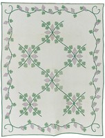 Green, lavender appliqué on white background with four-sided vine border. Separate green binding. Alternating blocks of appliqué and white work.