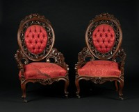 Pair of parlor chairs of carved rosewood, the upholstered oval back framed by pierced, carved S-scrolls, the upper crest rail with carved roses and daisies, this on carved S-scroll and rose supports, shield-shaped seats framed by serpentine seat rail with central carved floral element, on cabriole legs with scrolled front feet on casters, floral cartouches at shoulders, with red silk damask upholstery