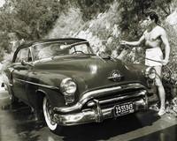 Rock Hudson Washing His car Outside His Hollywood Hills Home, Sid Avery, gelatin silver print