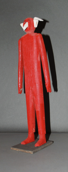 Standing wooden figure painted red with white nose, ears, and horns (a devil) on a wood base.