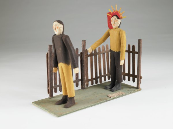 """Figues of Christ and Peter standing before a fence, a cock perched on the fence post, """"Please don't deny again Peter"""" written in pencil on a small wood plaque"""