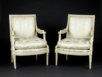 Pair of white painted beechwood armchairs in the neoclassical style, each with a rectangular padded back within a frame of carved lotus, or leaf-tip, molding with beaded toprail, which extends along the curved armrest to the padding, below the padding the scrolled handhold is decorated with a carved overlapping lozenge pattern, similar to coin molding, which extends down to the front chair rail, terminating in a stylized acanthus leaf, the bowed front rail and side rails likewise decorated in the same lozenge pattern, the legs in the shape of tapered, fluted columns headed by patera; the back is undecorated; the celery-green silk upholstery and cushion are modern.