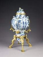 Perfume fountain comprised of three unrelated pieces of Chinese blue and white porcelain, each decorated with floral elements, set in gilt-bronze mounts; the main porcelain body baluster shaped and decorated at the shoulder with four pierced fu dog elements that hold chains in their mouths; these chains are attached to four detachable gilt-bronze spouts in the shape of dolphin heads, which have been inserted into the lower body; the porcelain cover is surmounted by a reclining fu dog with a gilt- bronze collar with chain attached to the body of the fountain; the lower part of the fountain is comprised of the third piece of porcelain, the cover of an object inverted and attached to the bottom of the main body with a gilt-bronze band; attached to this band are four cabriole legs with masks and stylized foliage at the knees and hoof feet that rest on block bases.