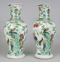Pair of Chinese porcelain famille-verte baluster vases.  Each painted with a pair of birds perched on a rock amidst chrysanthemms and bamboo, the reverse with flitting insects, the shoulders with a green swastika diaper border, and the trumpet-shaped neck with peonies and bamboo growing around rocks, double circle in underglaze blue