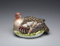 Porcelain covered tureen in the form of a partridge, naturalistically modeled and colored with a russet head and shaded brown plumage, resting on a white next edged in yellow wheatears, tan feathers and green grass.