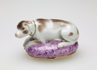 Small porcelain bonbonnière in the form of a recumbent dog with brown spots and a pale yellow collar lying on a puce patterned oval pillow, the cover exterior painted with a dog stalking birds, the rim and cover rim with a hinged gilt metal mount.