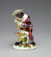 Figure of Harlequin seated on a tree stump on small base decorated with green leaves and colorful flowers, wearing a gray hat, his costume half yellow and half checkered in shades of blue, red, and black, wearing underneath a white shirt with ruffled collar and cuffs, his left hand is raised to his face, thumbing his nose, while his right hand twists the tail of a monkey, which is pinned under his right leg