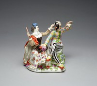 """Playful group of Harlequin and Columbine seated on a large rock encrusted with green leaves and colorful flowers, Columbine wears a small blue hat and gilt-dotted salmon-colored and black bodice with white ruffled collar, a red cloak with gray lining and a white skirt painted with """"indianische Blumen,"""" her left hand tweaks the nose of Harlequin's mask, while in her right hand she holds a slapstick poised to hit him; Harlequin wears white trousers with black stripes, red shoes with yellow bows, and a checkered tunic in shades of lilac, yellow, and turquoise with green bows down the front, his legs are crossed, his right hand rests on his plumed black hat, which is lying on Columbine's lap, in his raised left hand he holds a sausage"""