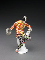 """Figure of Harlequin seated on a white tree stump on small base, his left leg resting on side of stump while his right leg rests on the ground, his right arm is outstretched and he holds his upturned gray hat in his hand, in his left hand he holds a white and gilt open tankard, which rests on his upper thigh, this with the date """"1740"""" in gold; he wears trousers in a checkered pattern in lilac, green, and black, and red shoes with blue bows, his tunic is incised in a checkered pattern, which the painter did not follow exactly, and is painted in red, yellow, and white with gilt buttons, he wears a half mask covering his upper face"""