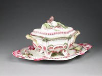 Large oval faience soup tureen with matching cover and stand, the tureen molded with scrolls, gadrooning, and shellwork decorated in rose, or pink-purple (pourpre de Cassius), and green enamel on a white ground, with four scrolled feet similarly decorated, the handles are molded with feathers and are enameled in shades of yellow and rose; the domed quatrefoil lid is similarly decorated and has an elaborate knop in the shape of naturalistically molded celery, peas, mushrooms, and mussels; the stand with two intertwined and pierced handles in shades of rose and likewise molded with scrolls and shellwork, also enameled in blue and yellow with a green, molded artichoke sprig in the center and with mushrooms and crustaceans at either end.