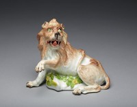 Porcelain figure of a lion with a tan coat, a grey nose, chartreuse-green eyes and an open mouth revealing an iron-red tongue, with a raised left forepaw, semi-recumbent on a mound base applied with yellow florettes and green leaves, mounted on a gilt bronze rococo scrollwork base.