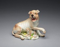Porcelain figure of a lioness with a tan coat, a grey nose, chartreuse-green eyes and an open mouth revealing an iron-red tongue, with a raised right forepaw, a cub beneath her breast, semi-recumbent on a mound base applied with yellow florettes and green leaves, mounted on a gilt bronze rococo scrollwork base.